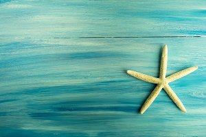 White starfish on blue wooden board