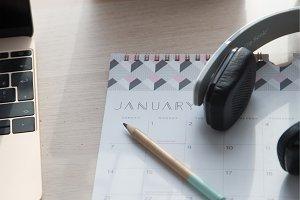 Calendar and headset next to laptop