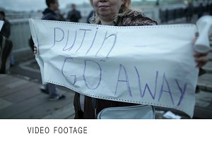 Woman holds a placard Putin Go Away.