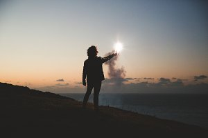 Man holding flare on edge of cliff