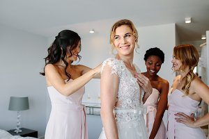 Friends dressing the bride for weddi