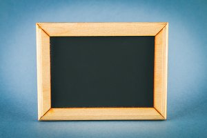 Chalkboard in a wooden frame with an empty box on a gray background. Copy the space.