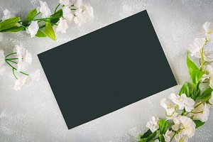 Chalkboard with an empty field surrounded by white flowers on a gray background. Copy the space. Template for spring or female holiday.