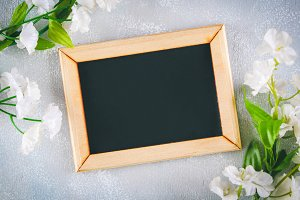 Chalkboard in a wooden frame with an empty box surrounded by white flowers on a gray background. Copy the space. Template for spring or female holiday.
