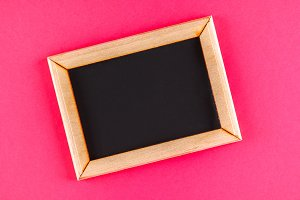 Chalkboard in a wooden frame with an empty box on a pink background. Copy space.