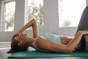 Smiling female lying on exercise mat