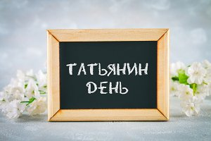 The inscription in Russian: Tatyanin day. Russian holiday on student's day. A chalkboard is surrounded by white flowers on a gray background.