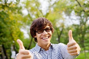 Guy showing thumbs up in park