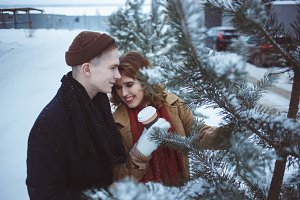 Young couple embracing among trees covered snow. Leisure activity in park. Coffee cups in hands.
