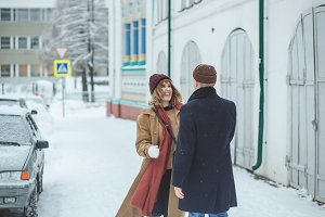 Young beautiful couple lovers hugging, laughing and has a fun winter time in a snow winter city. Winter holidays, love concept