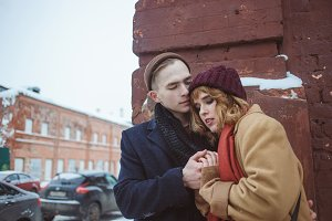 Young man and woman embracing near brick corner of building. Winter street. Privacy in the secluded places of the big city