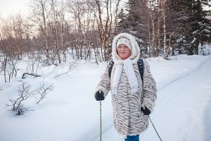 Winter sport - nordic walking. Senior woman hiking in cold forest. Happy ruddy face, healthy circulation . Cardio training