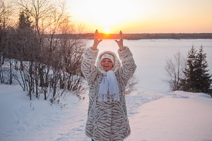 Portrait of a senior woman holding winter sun. Cheerful woman in winter sun rays