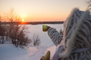 Warm clothed woman holding cup of hot drink at winter sunset.