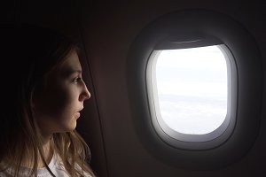Girl sitting by aircraft window and looking outside.