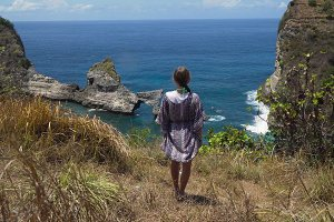 Girl standing on a cliff and looking at the sea. Bali, Indonesia