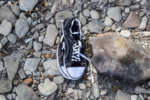 Black and white sneakers on stones. Sport shoes.