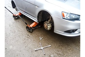 The car is at the tire shop. Under the jack the car in car-care center. The car with the removed wheel.