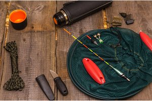 Tools and accessories for fishing. View from above. Wooden background.
