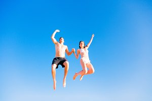 Young Couple In Swimwear Jumping