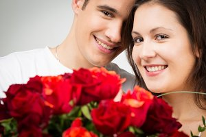 Happy Valentine's Couple Holding Bouquet Of Roses
