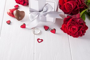 Fresh red roses and gift box on wooden table