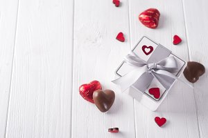 candies hearts and gift box on wooden board,