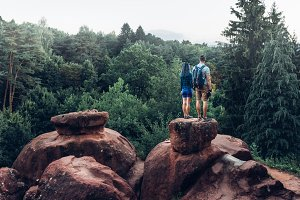 Young Couple, Men And Women Of Backpackers Standing On Top Of Mountain And Enjoying View Of Nature In Summer