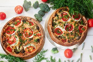 cheese cake with broccoli, green beans, tomatoes and Dill on white wooden table