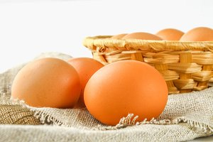 Raw brown chicken eggs in a basket on burlap on a white wooden table. Ingredients for cooking.