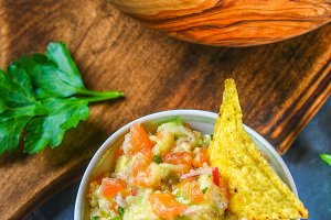 Guacomole is a traditional Mexican sauce consisting of grated avocado, lime juice, red onion, tomatoes, garlic and chili. Served with nachos chips.