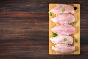 Raw chicken fillets on a cutting board against the background of a wooden table. Meat ingredients for cooking. Empty place for an inscription. Copy the space. Flat lei. Top view.