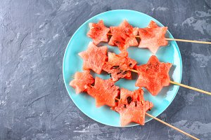 Watermelon in the form of stars on skewers lies on a plate. The blue dish is like a rocket in space. Top view.