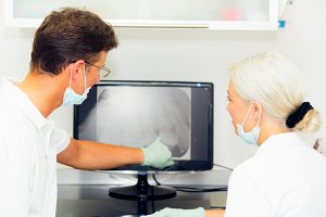 Dentist And Assistant Looking At Dental X-ray