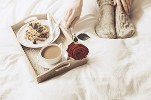 Woman taking rose from tray with breakfast