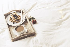 Tray with sweet breakfast and rose