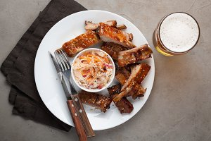 Grilled pork ribs in barbecue sauce and honey with sauerkraut and beer on a white plate. Snack to beer on a light stone table. Top view
