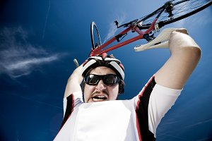 Man Wearing Helmet And Lifting Bicycle Into Air