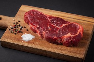 Beef steak on the wood black background. Horizontal photo. Food background. Marble the meat with pepper and salt on a dark background