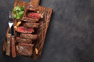 Closeup ready to eat steak new York beef breeds of black Angus with herbs, garlic and butter on a wooden Board. The finished dish for dinner on a dark stone background. Top view with copy space
