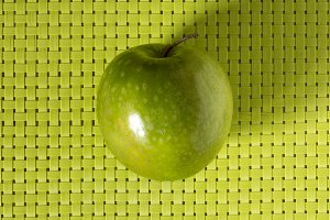 Green apple on checkered texture