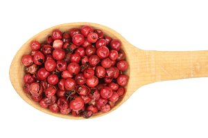 red peppercorns seeds in wooden spoon isolated on white background. Top view. Flat lay