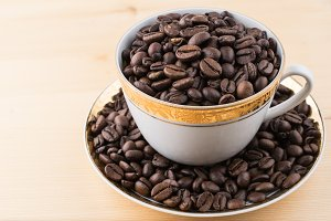 Cup and saucer filled with coffee beans on wooden table