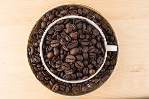 Cup and saucer filled with coffee beans on wooden table from above