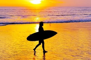 Woman surfer walking beach Bali