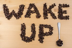 sign wake up made of coffee beans on wooden table spoon