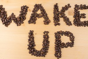sign wake up made of coffee beans on wooden table