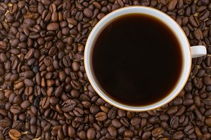 White cup of black coffee coffee beans from above