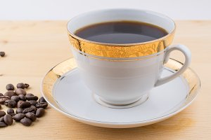 White cup of black coffee on saucer with roasted coffee beans on table