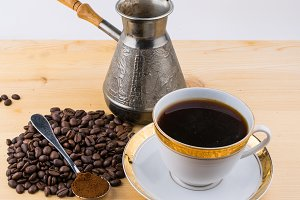 White cup on saucer turk spoon with ground coffee and coffee beans on wooden table